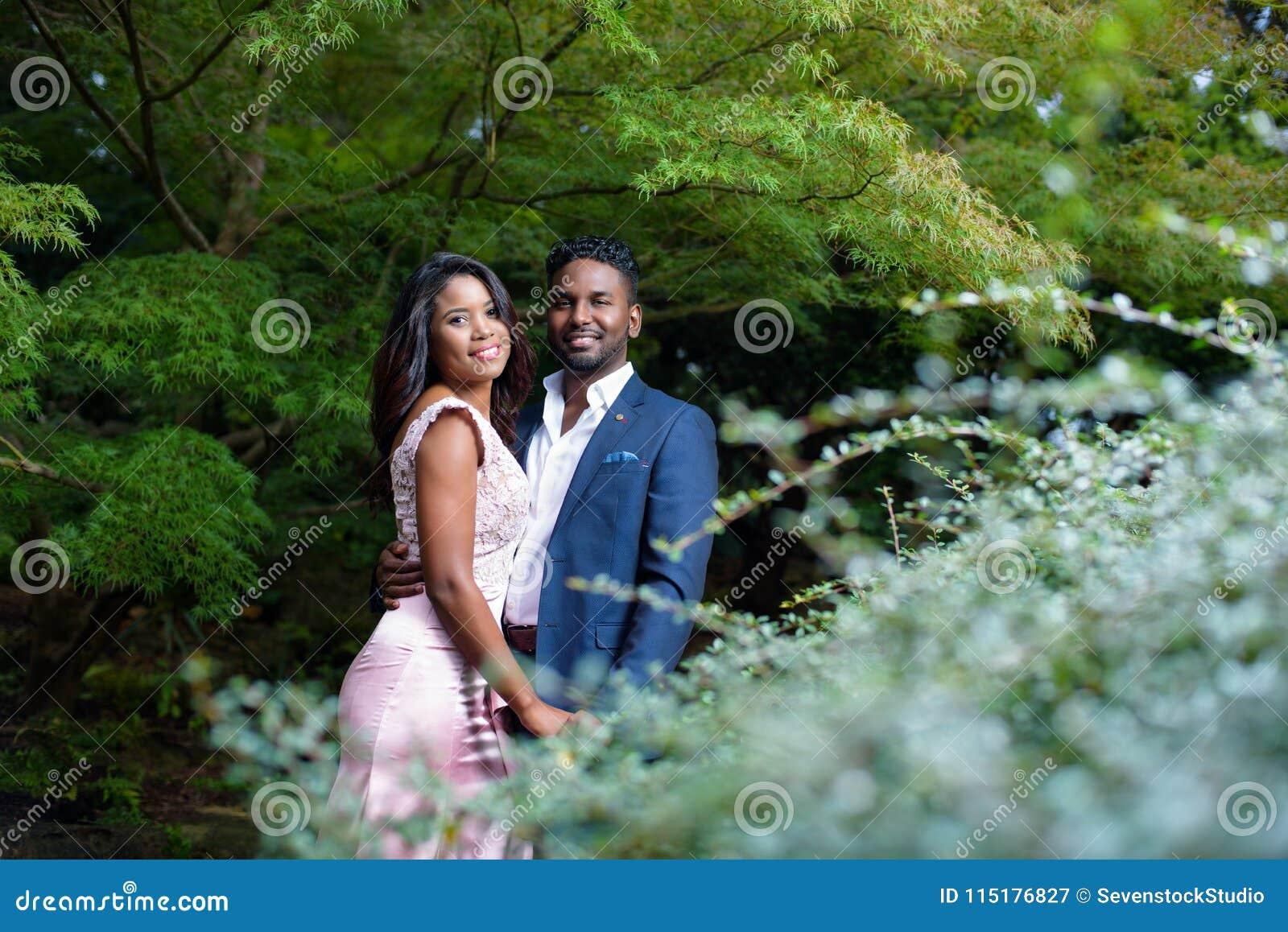 Portrait de jeunes couples heureux dans un jardin avec le beau feuillage