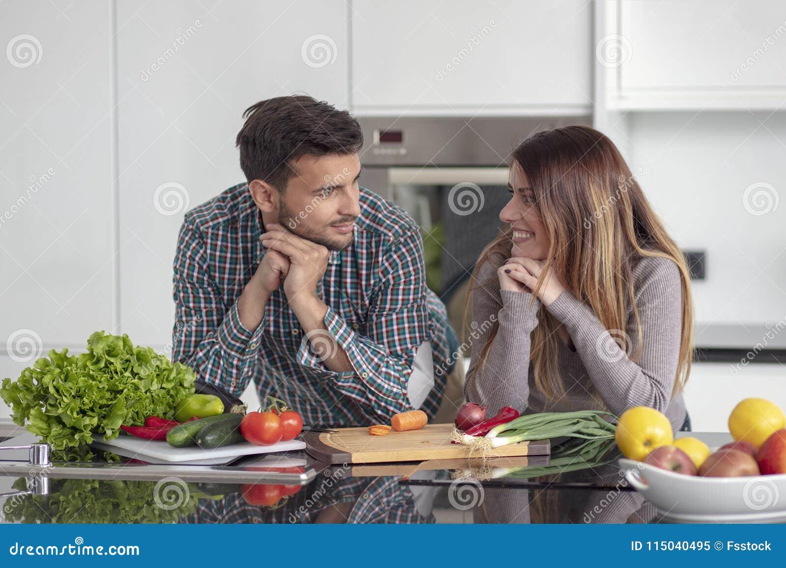 Portrait de jeunes couples heureux faisant cuire ensemble dans la cuisine à la maison