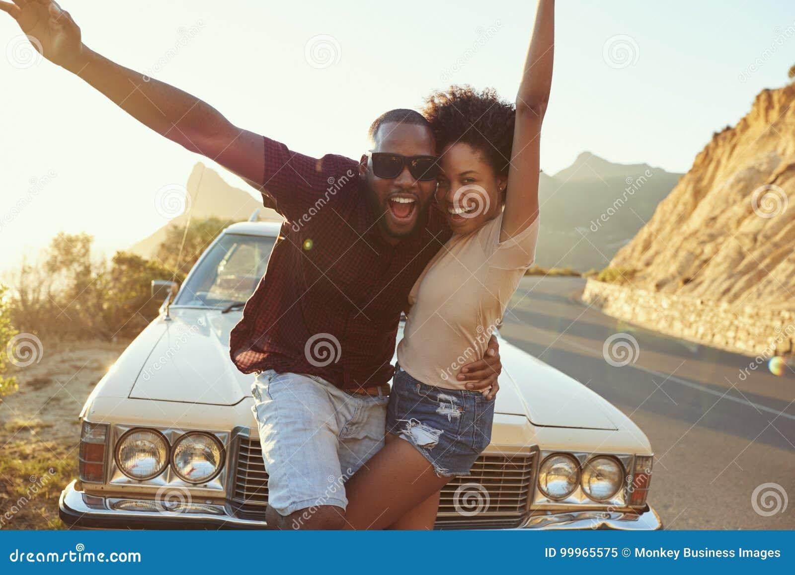 Portrait de jeunes couples se tenant à côté de la voiture classique