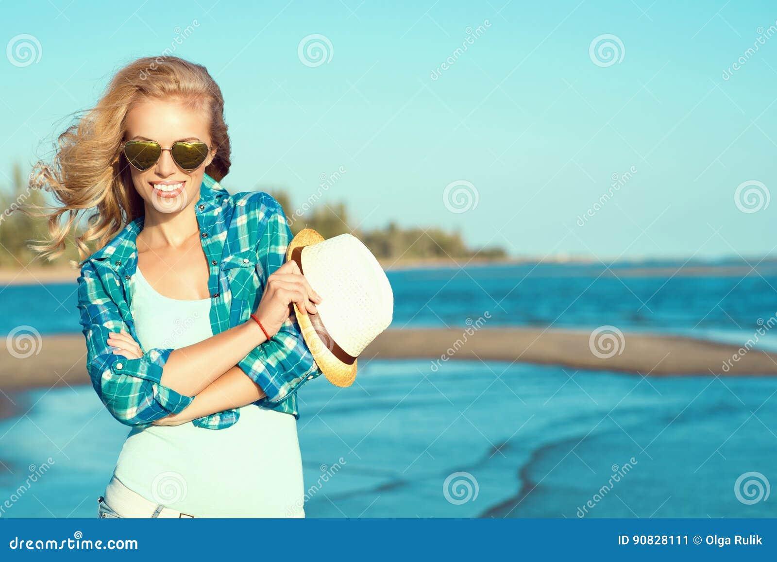 Portrait de jeunes lunettes de soleil en forme de coeur reflétées de port blondes bronzées sexy magnifiques et de chemise bleue v