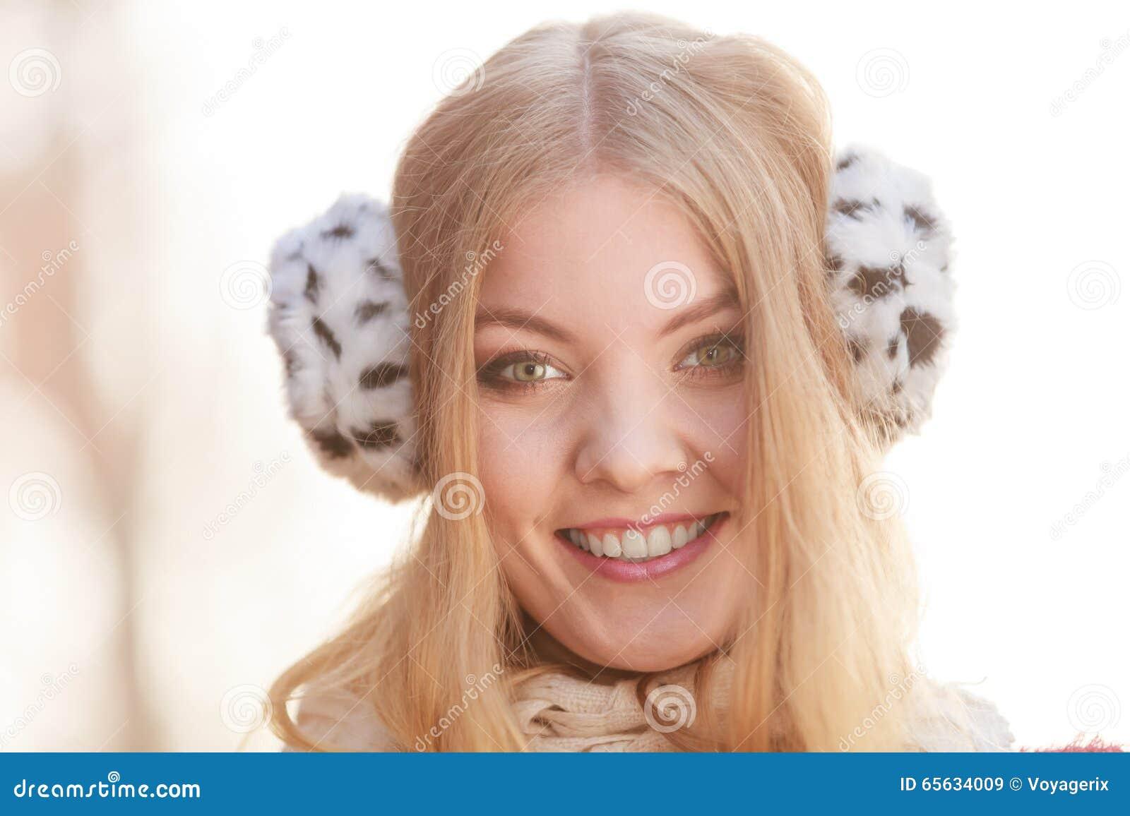 Portrait de jolie femme de sourire dans des bouche-oreilles de fourrure