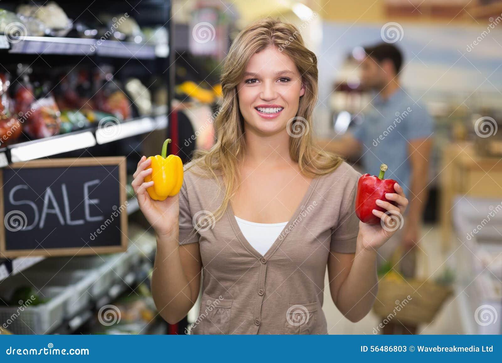 Portrait de jolis légumes de achat de sourire d une femme blonde