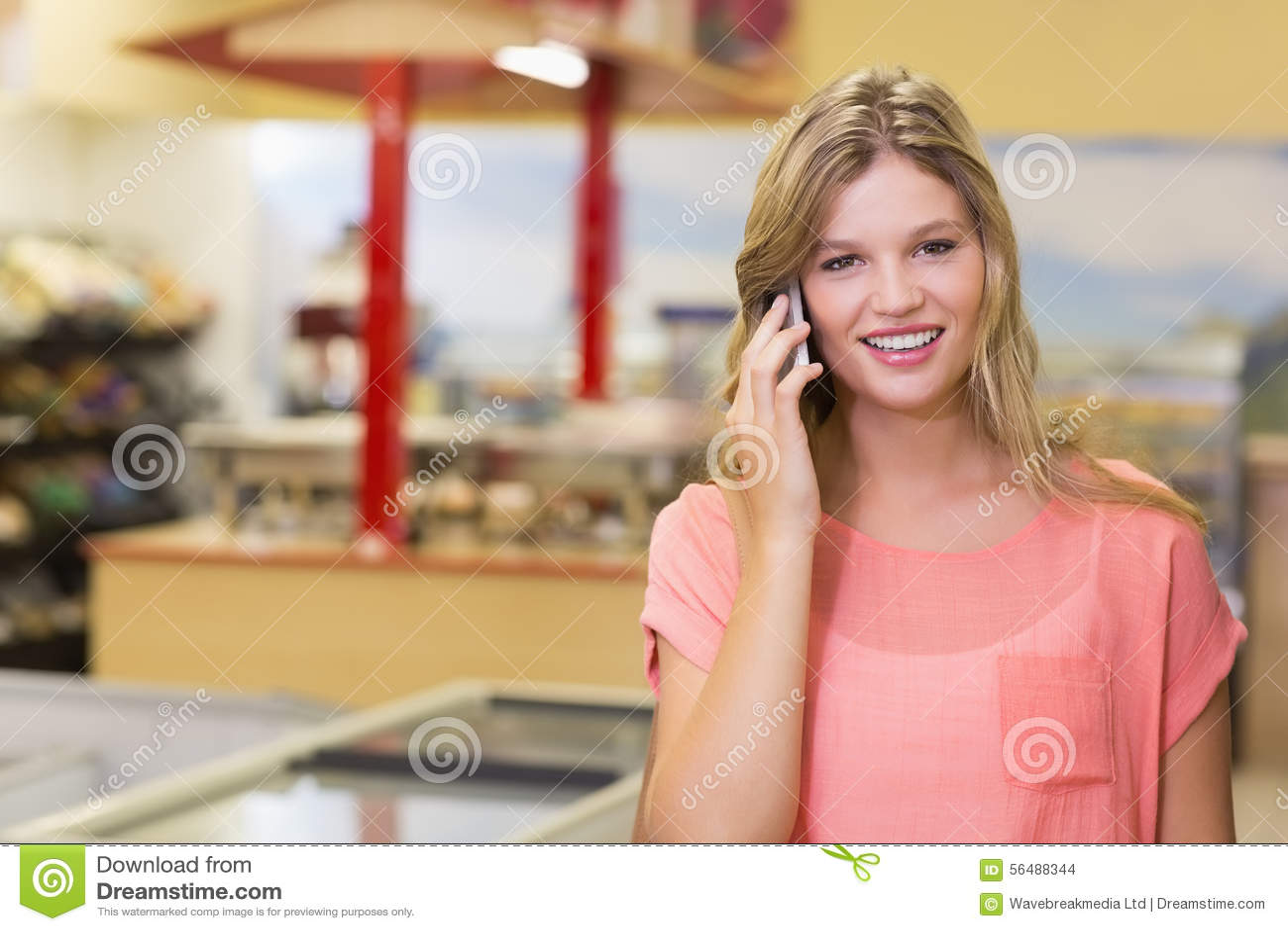 Portrait de jolis produits de achat de sourire et de téléphoner d une femme blonde