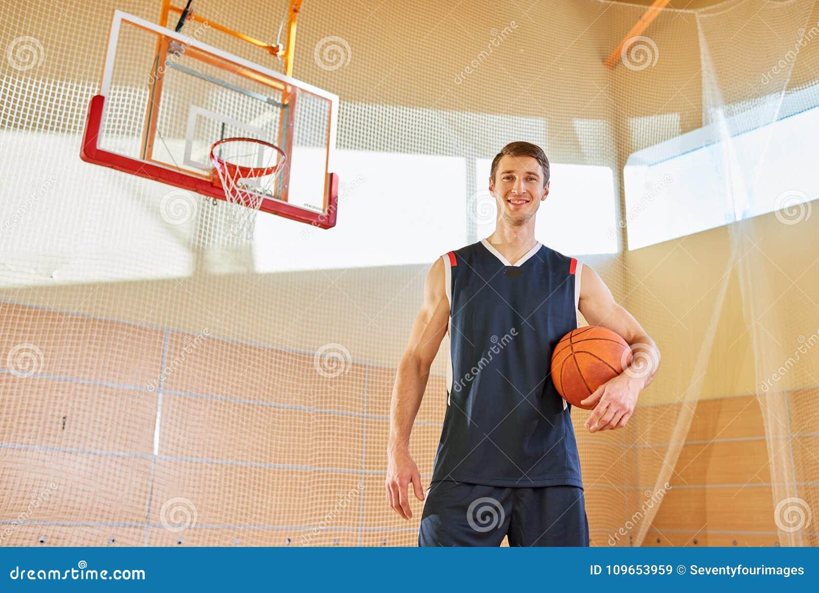 Portrait de joueur de basket grand beau heureux sur la cour