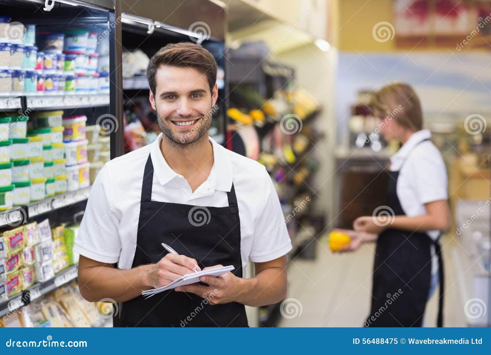 Portrait de l écriture de sourire d homme de personnel sur le bloc-notes