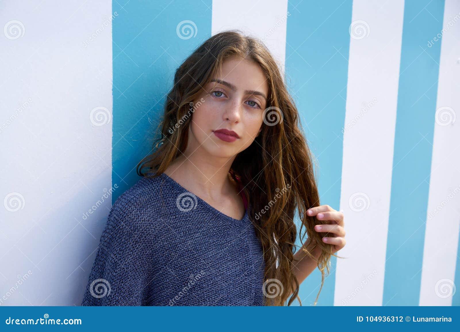 Portrait de l adolescence de fille de brune dans le mur de rayures bleues