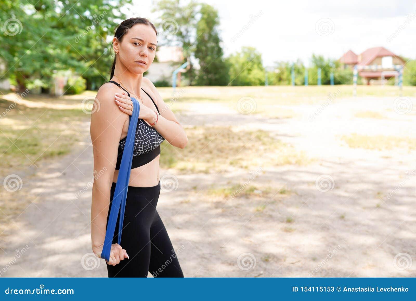Portrait de l ajustement et de la jeune femme sportive faisant l ?tirage dans la ville
