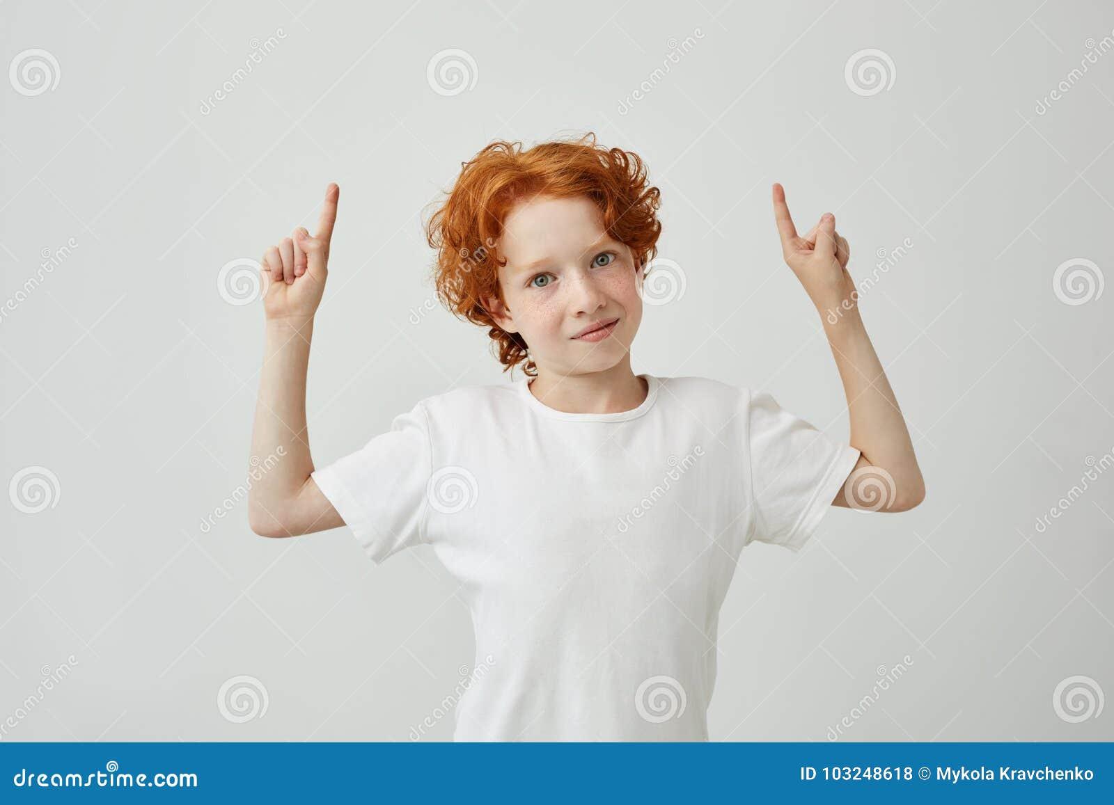 Portrait de l enfant drôle de gingembre avec des taches de rousseur dirigeant la partie supérieure sur le mur blanc avec l espace