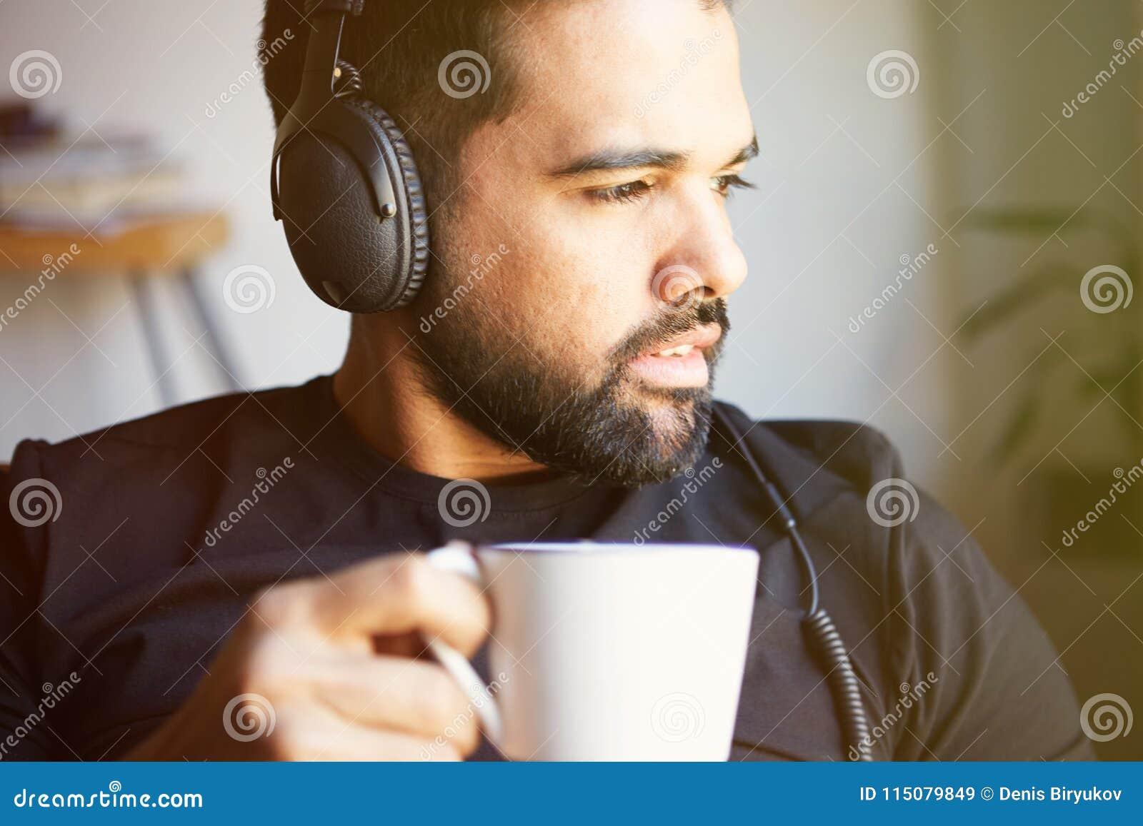 Portrait de l homme barbu bel dans des écouteurs écoutant la musique à la maison et le café potable Temps de détente et de repos