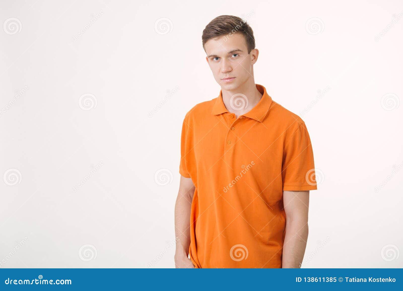 Portrait de l homme châtain bel utilisant la chemise orange semblant la position paisible au-dessus du fond blanc
