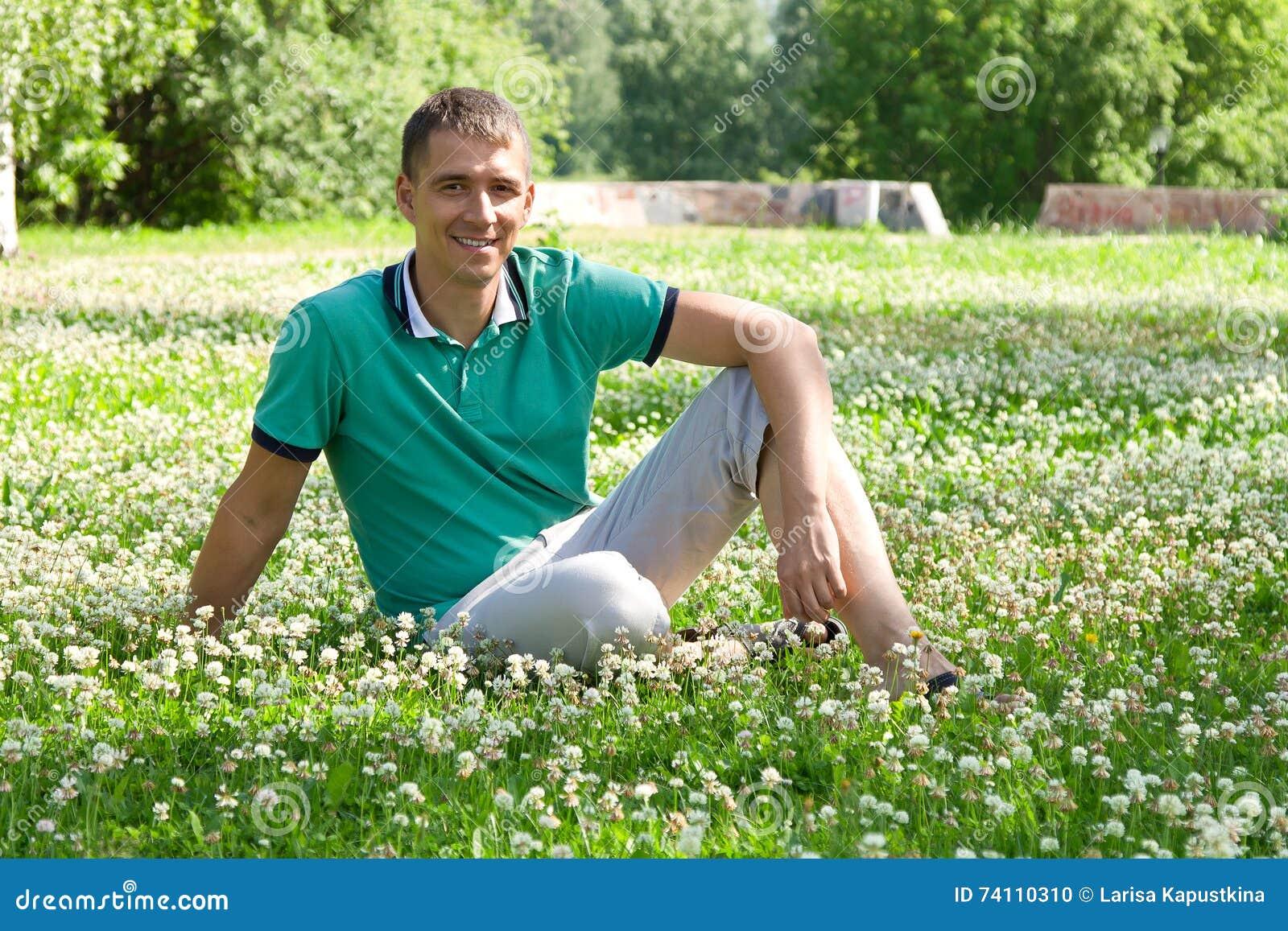 Portrait de l homme heureux attirant s asseyant sur l herbe dehors