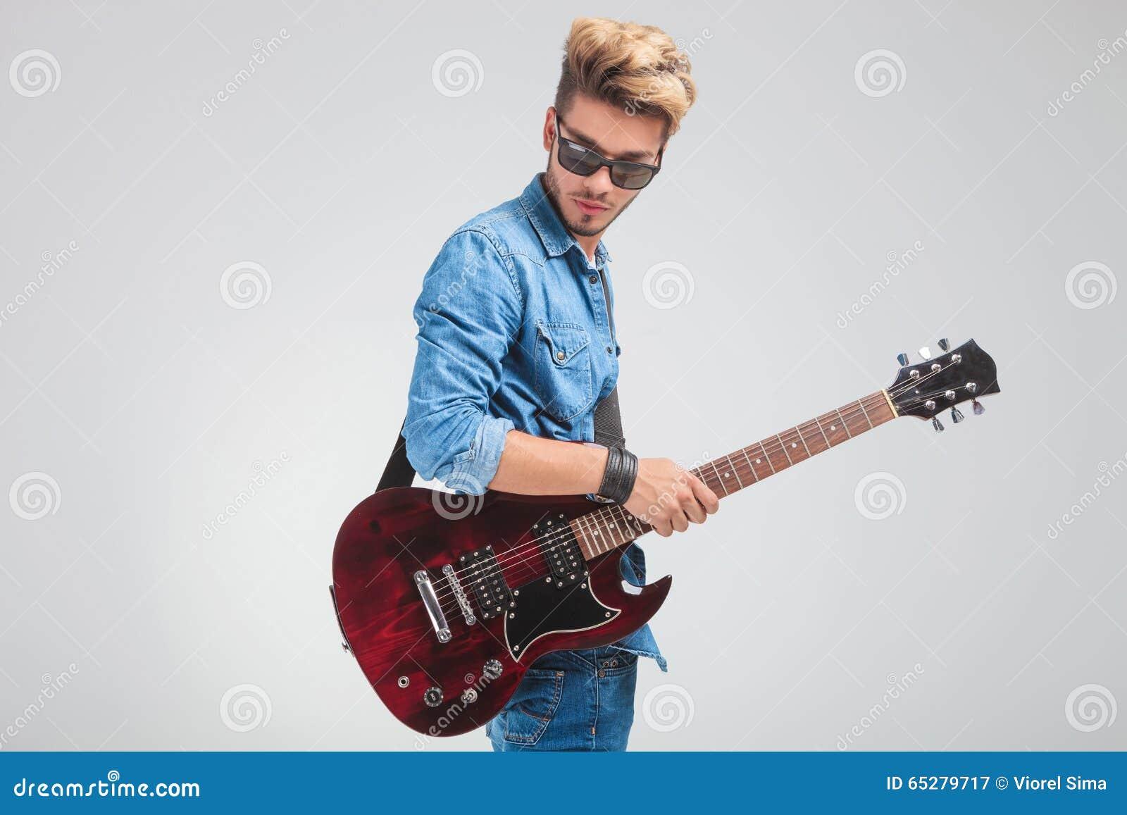 Portrait de l homme regardant vers le bas dans le studio tout en tenant une guitare