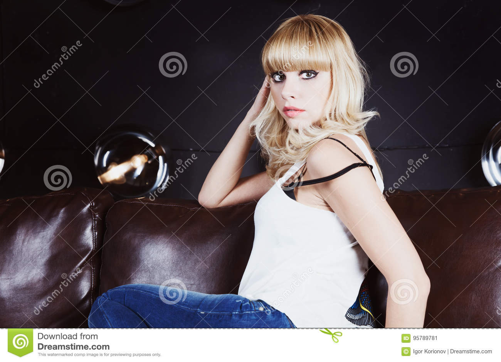 Portrait de la belle fille blonde s asseyant sur le sofa