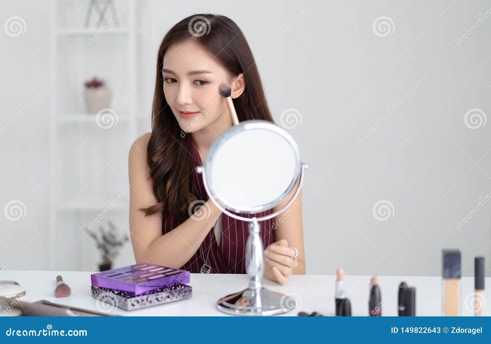 Portrait de la belle jeune femme asiatique faisant le maquillage regardant dans le miroir et appliquant le cosmétique avec une br