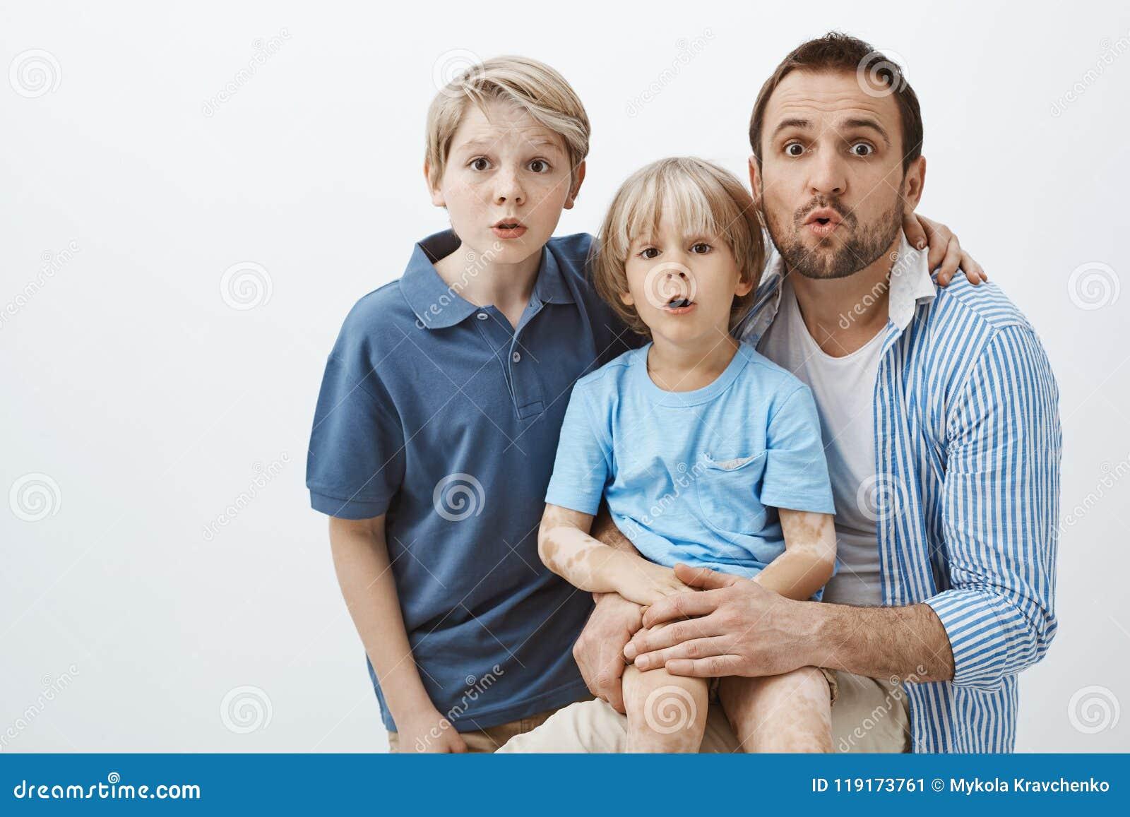 Portrait de la famille mignonne des fils et du père, étreignant et se tenant étonnée au-dessus du fond gris, mâchoire de chute, s