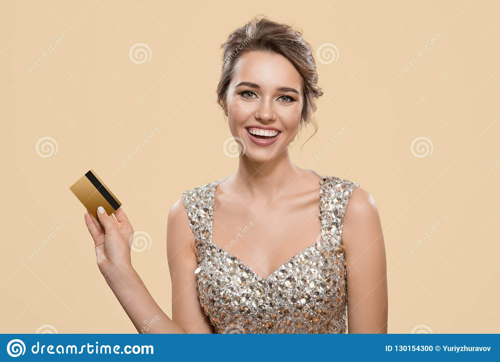 Portrait de la femme avec du charme heureuse tenant la carte de banque en plastique d or