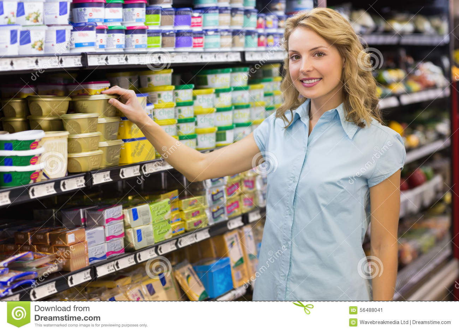 Portrait de la femme blonde de sourire prenant un produit dans les étagères