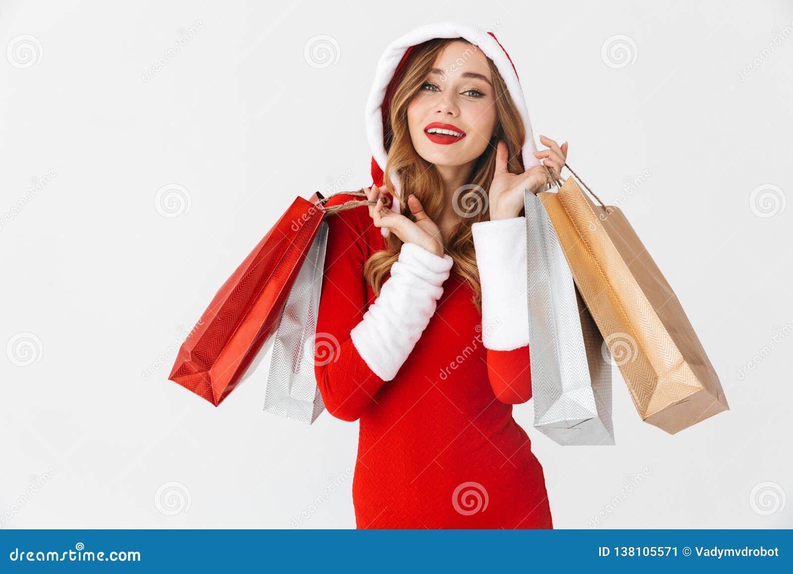 Portrait de la femme gaie 20s utilisant le costume rouge de Santa Claus souriant et tenant les sacs à provisions de papier coloré