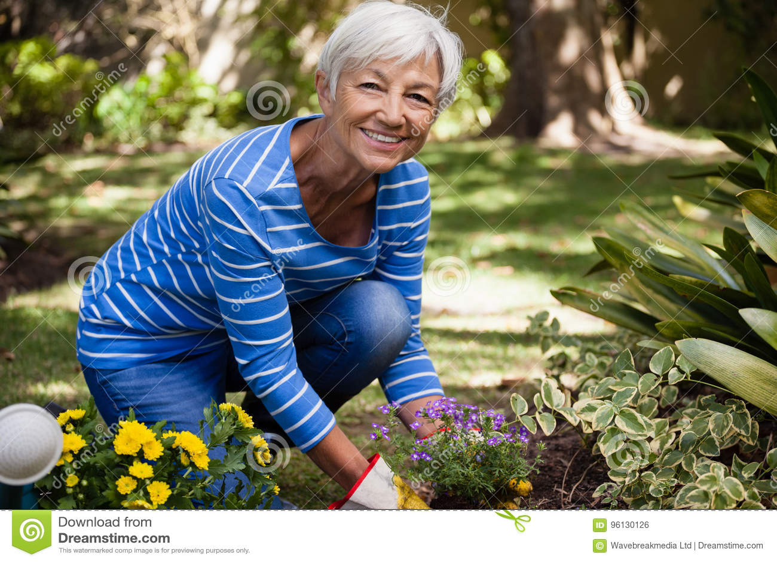 Portrait de la femme supérieure heureuse se mettant à genoux tout en plantant fleurit