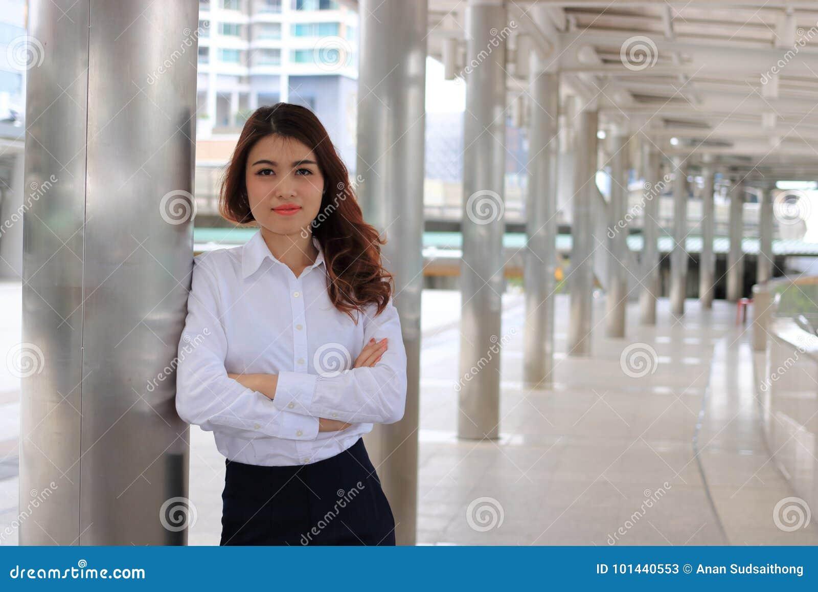 Portrait de la jeune femme asiatique attirante d affaires se penchant un poteau à l arrière-plan urbain de bâtiment