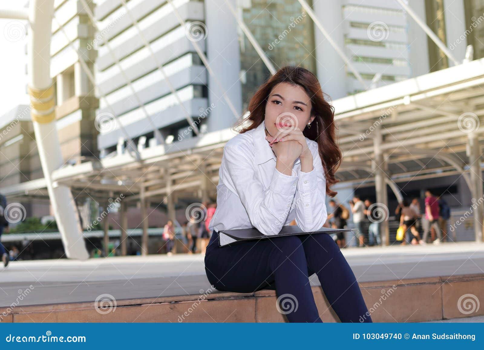 Portrait de la jeune femme asiatique d affaires de chef pensant et s asseyant sur l escalier à l arrière-plan urbain de bâtiment