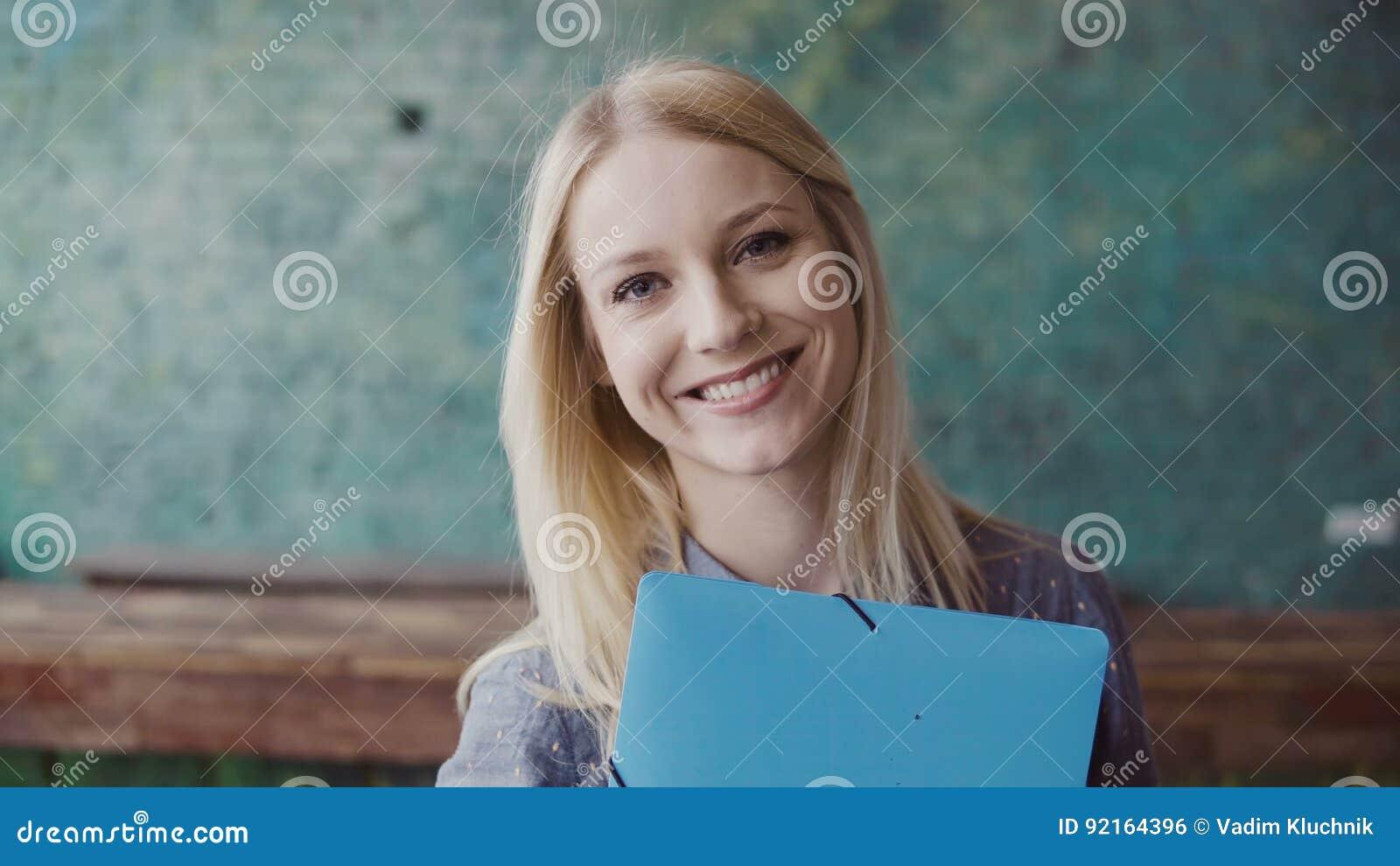 Portrait de la jeune femme blonde caucasienne regardant l appareil-photo et souriant au bureau moderne Employé réussi au travail