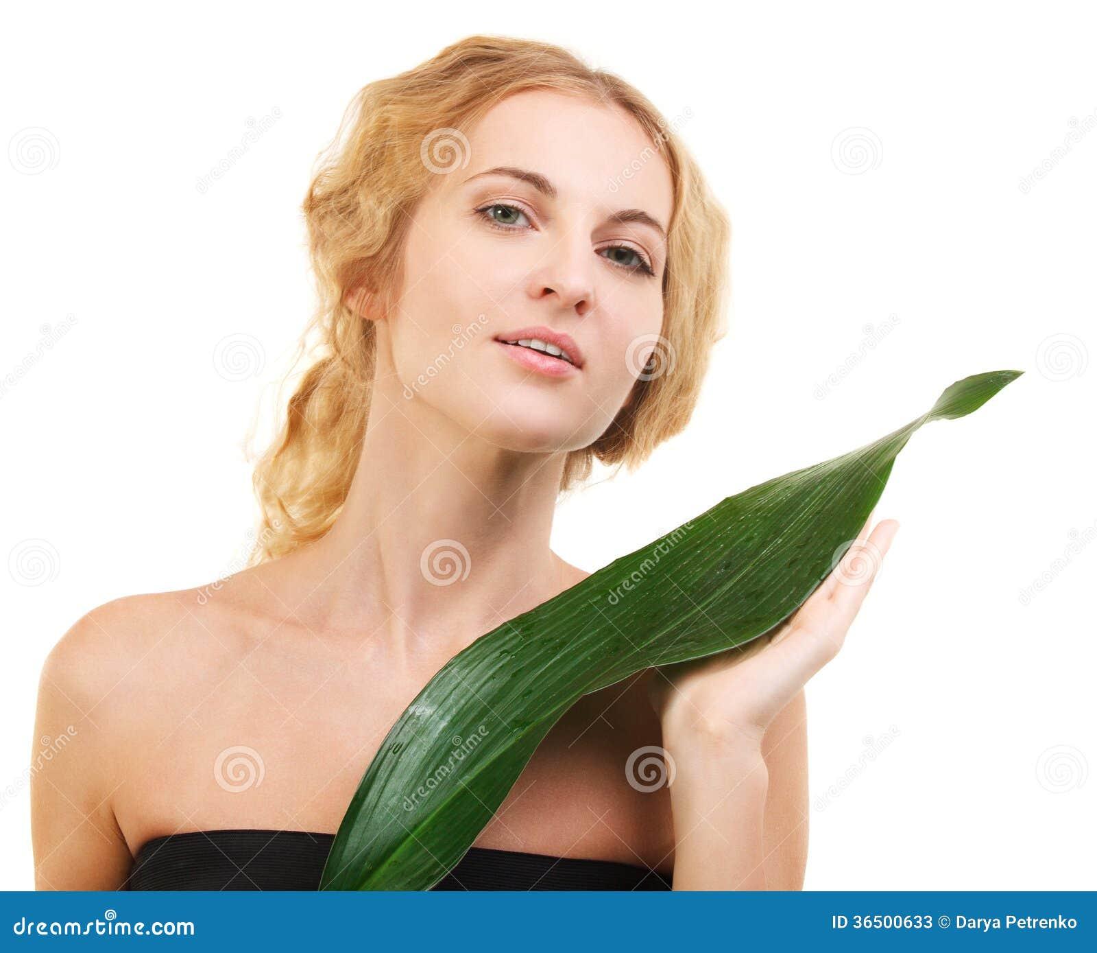 Portrait de la jeune femme blonde de beauté avec la feuille verte