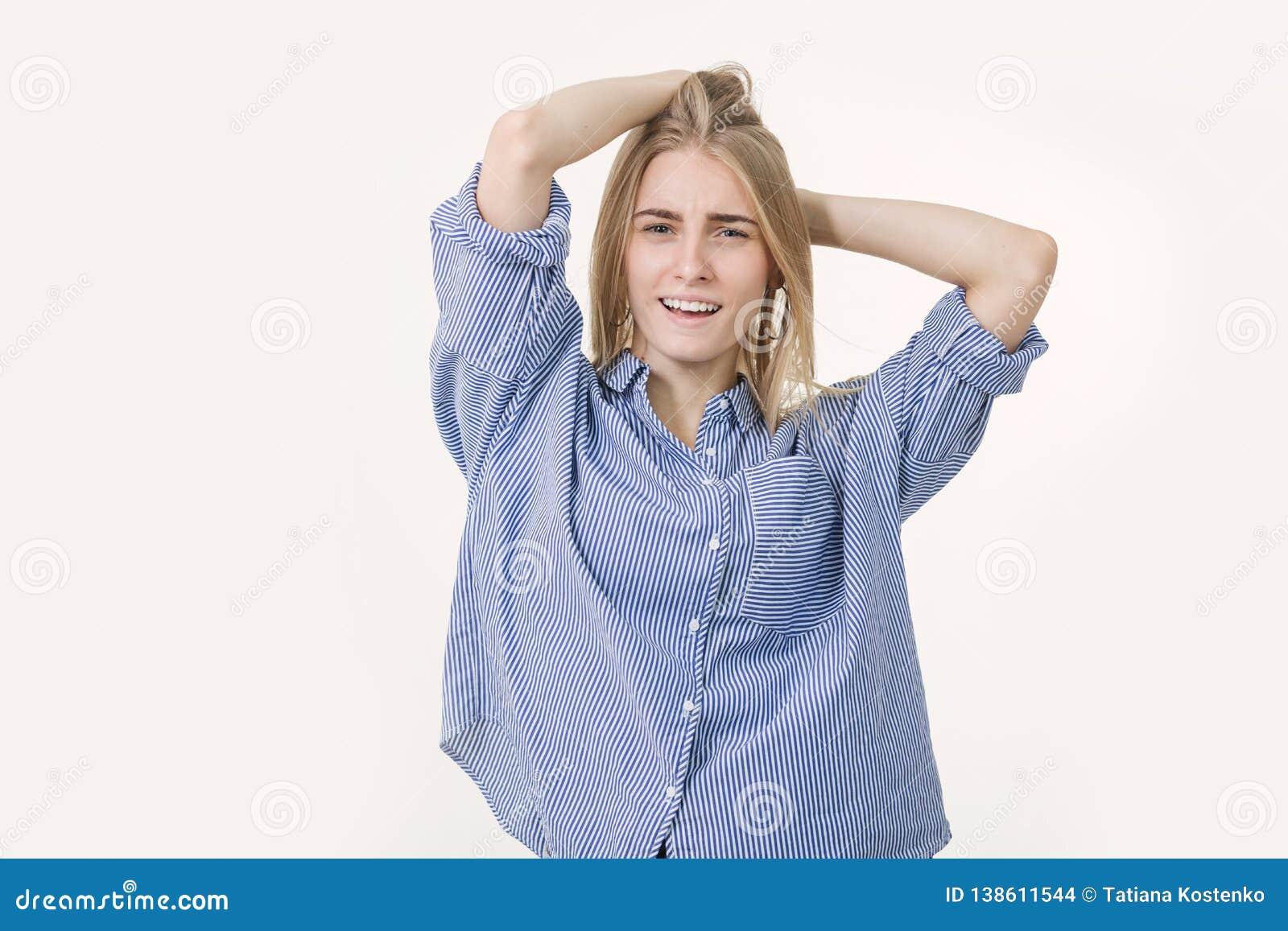 Portrait de la jeune femme blonde gaie utilisant la chemise bleue sur le fond blanc