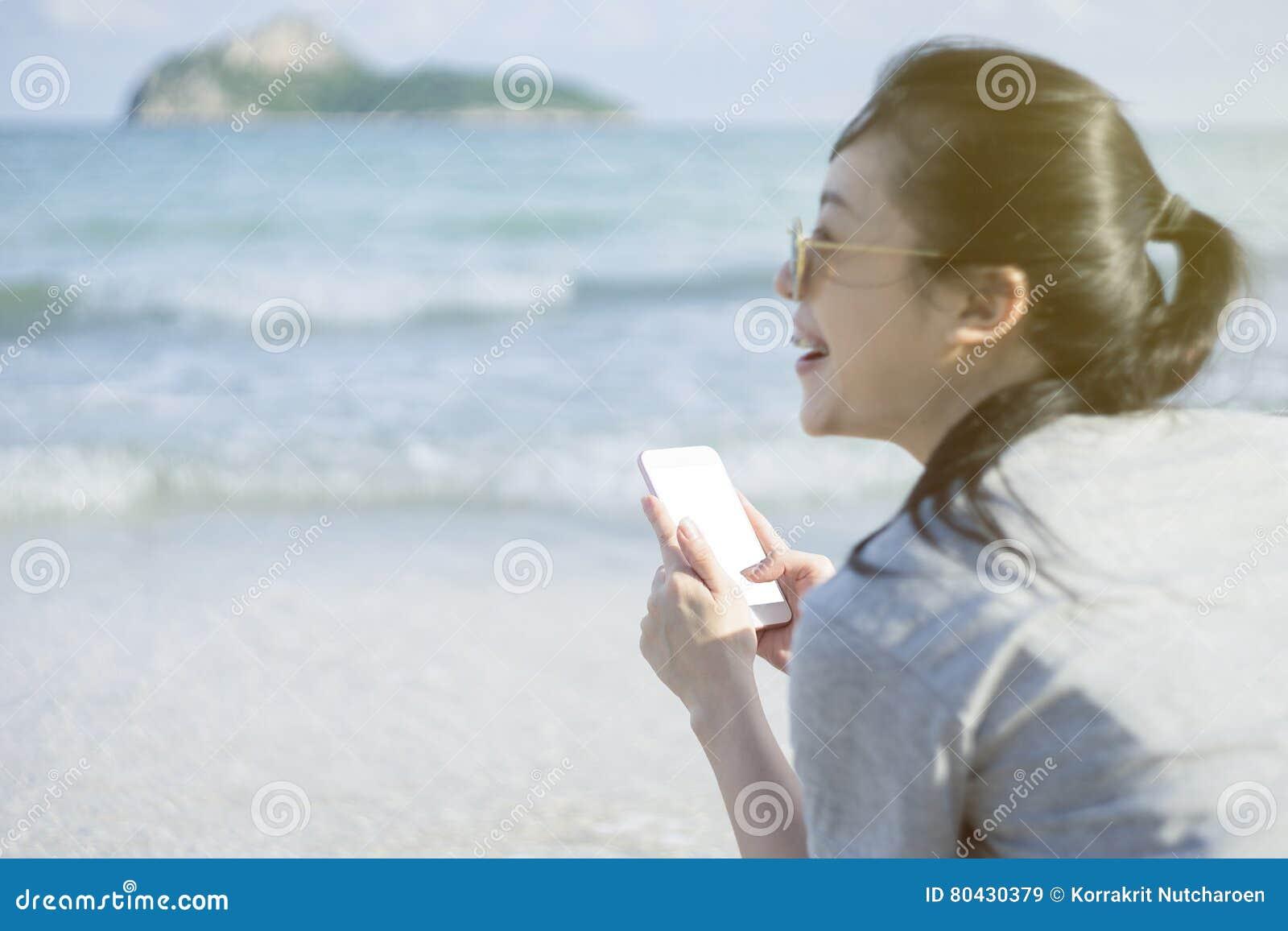 Portrait de la jeune femme heureuse asiatique à l aide du téléphone intelligent à la plage Concept de technologie fond brouillé d