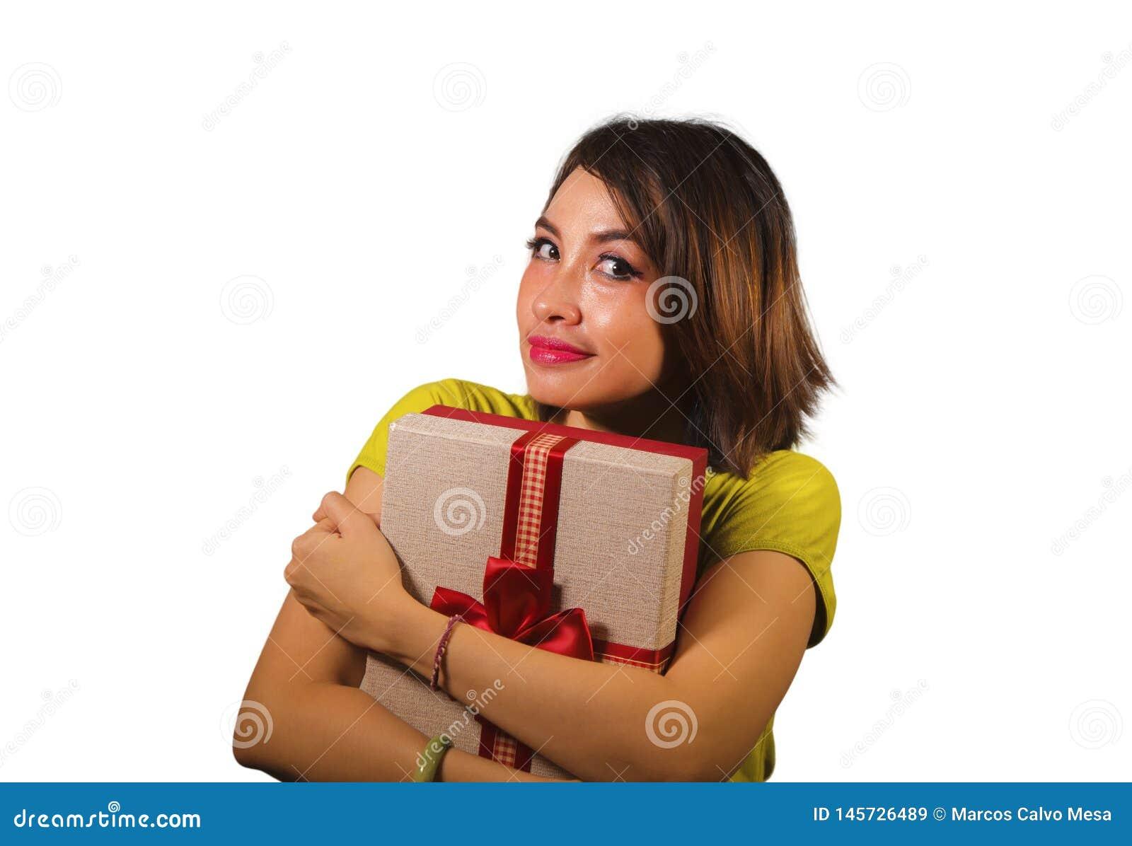 Portrait de la jeune femme indon?sienne asiatique heureuse et belle tenant le bo?te-cadeau de cadeau de No?l ou d anniversaire av