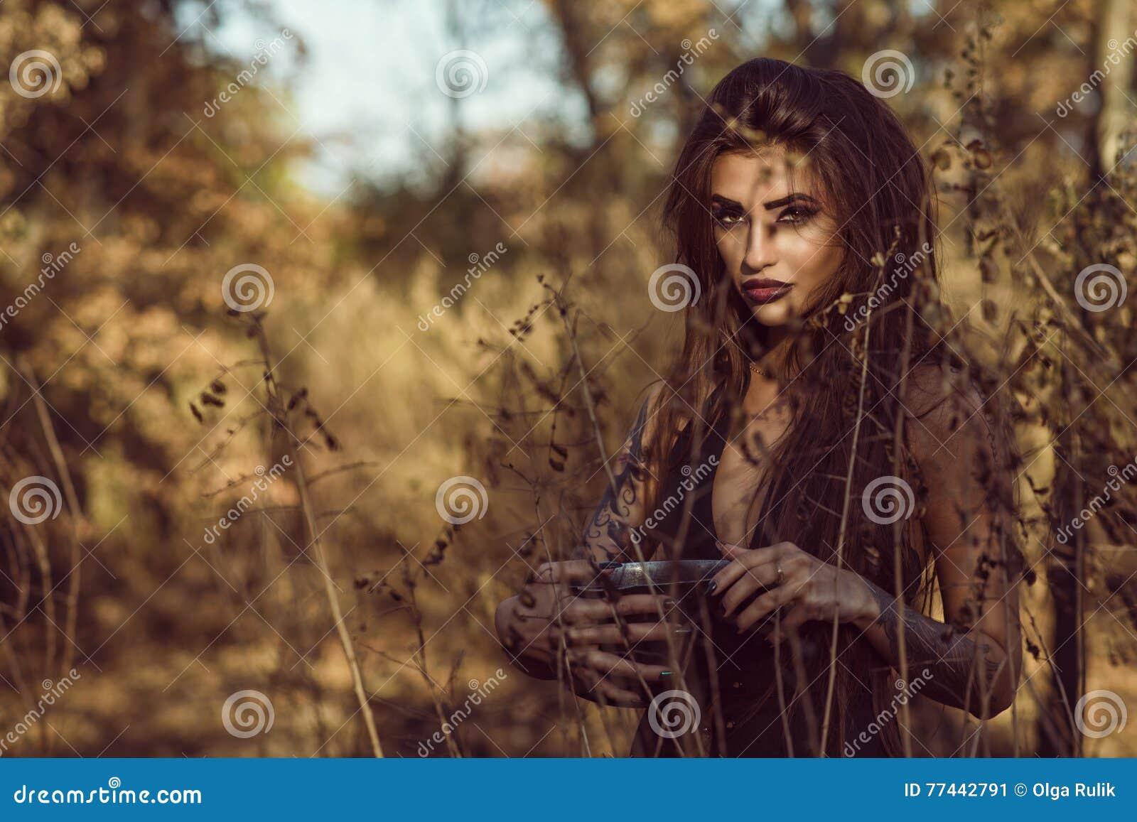 Portrait de la jeune sorcière dangereuse avec du charme tenant un pot avec le breuvage magique magique dans les bois et regardant