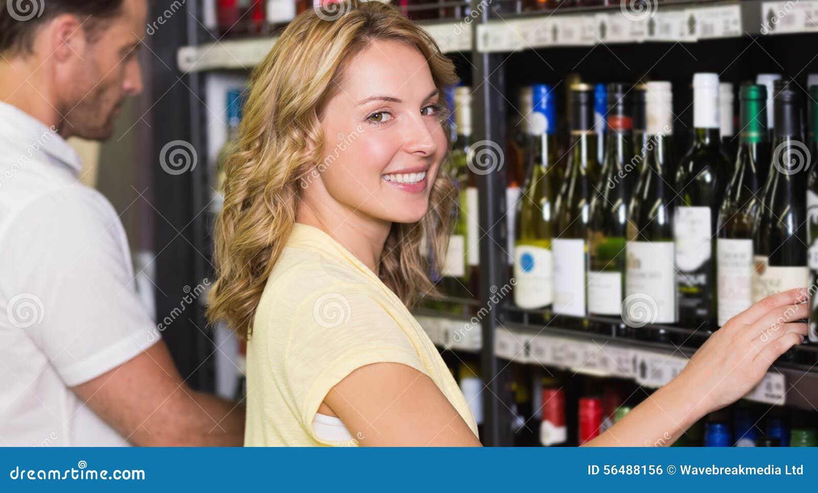 Portrait de la jolie femme de sourire achetant une bouteille de vin
