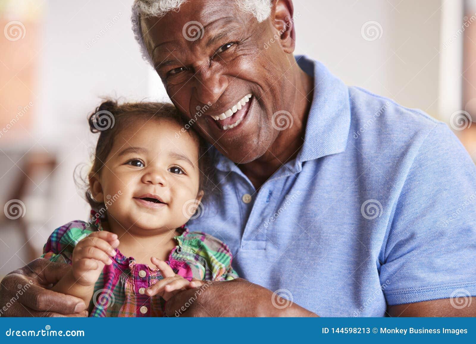 Portrait de la s?ance premi?re g?n?ration de sourire sur la petite-fille de Sofa At Home With Baby