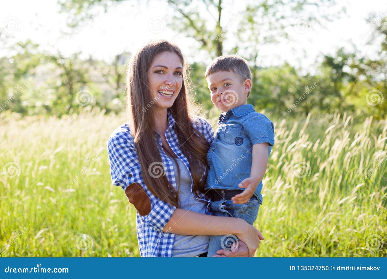 Portrait de mère et de fils contre la famille verte d arbres