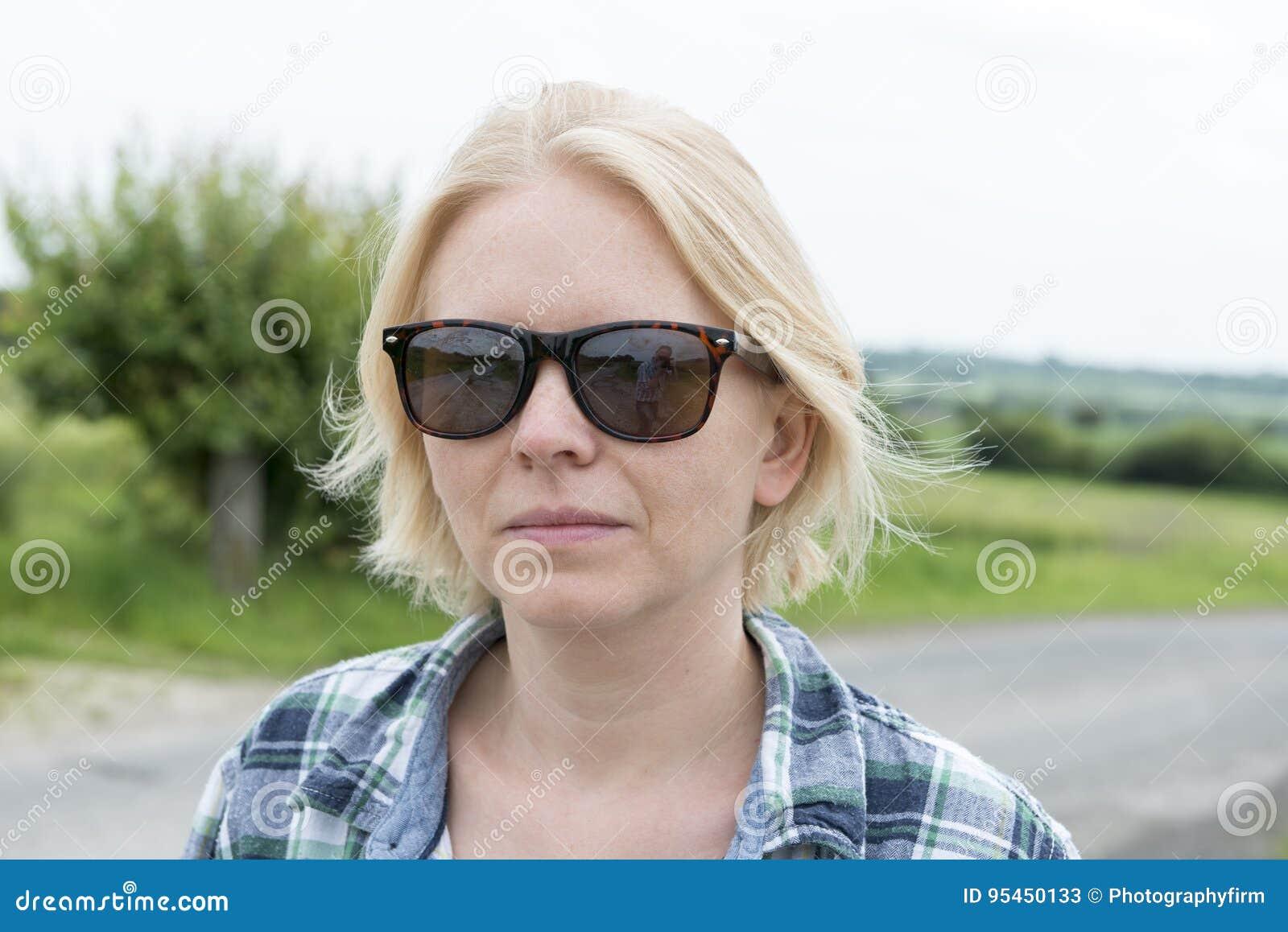 Portrait de Madame dans des lunettes de soleil dans l extérieur