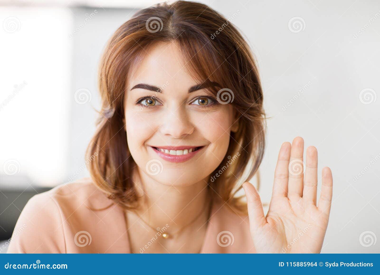 Portrait de main de ondulation de sourire de jeune femme