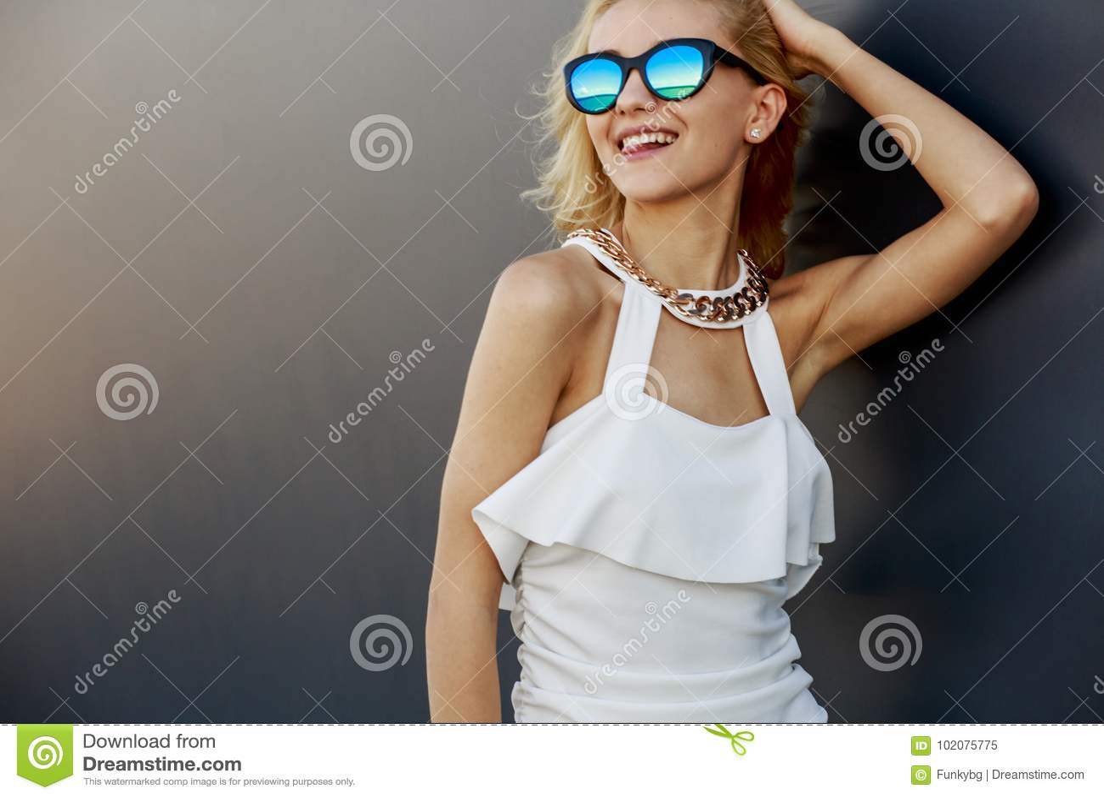 Portrait de modèle assez blond de jeunes dans des lunettes de soleil élégantes de miroir frais