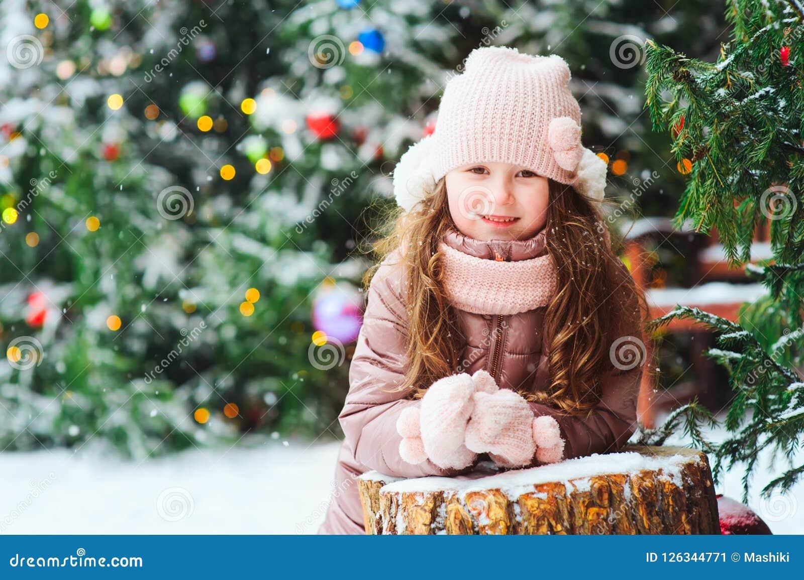 Portrait de Noël de jouer heureux de fille d enfant extérieur dans le jour d hiver neigeux, sapins décorés pendant des vacances d