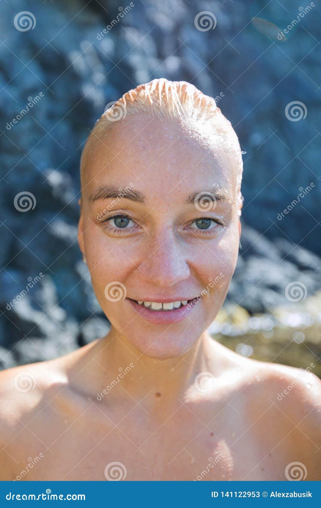 Portrait de personne féminine attirante avec les cheveux slicked humides et d épaules nues contre la roche côtière