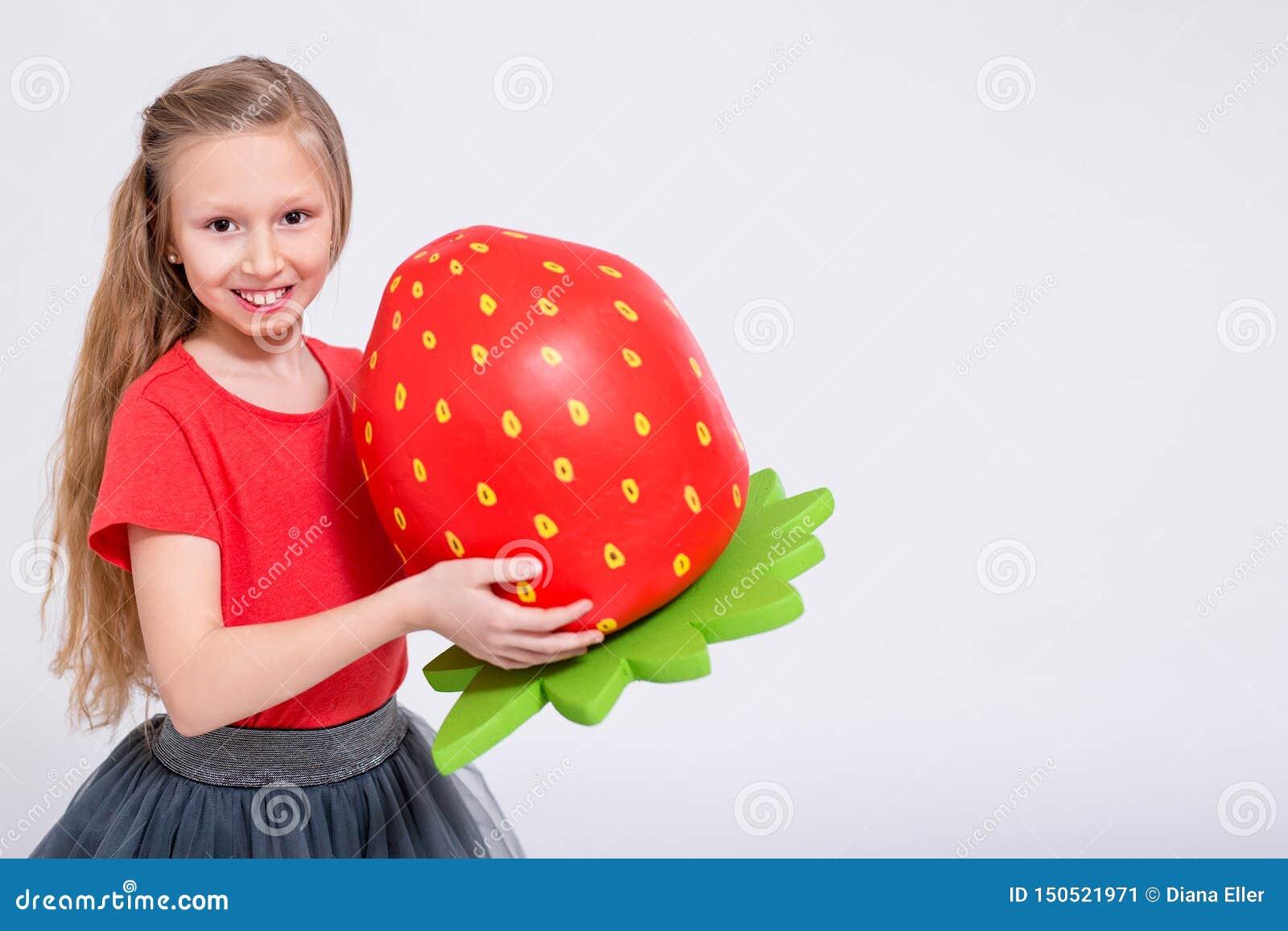 Portrait de petite fille mignonne avec le grand espace artificiel de fraise et de copie au-dessus du blanc