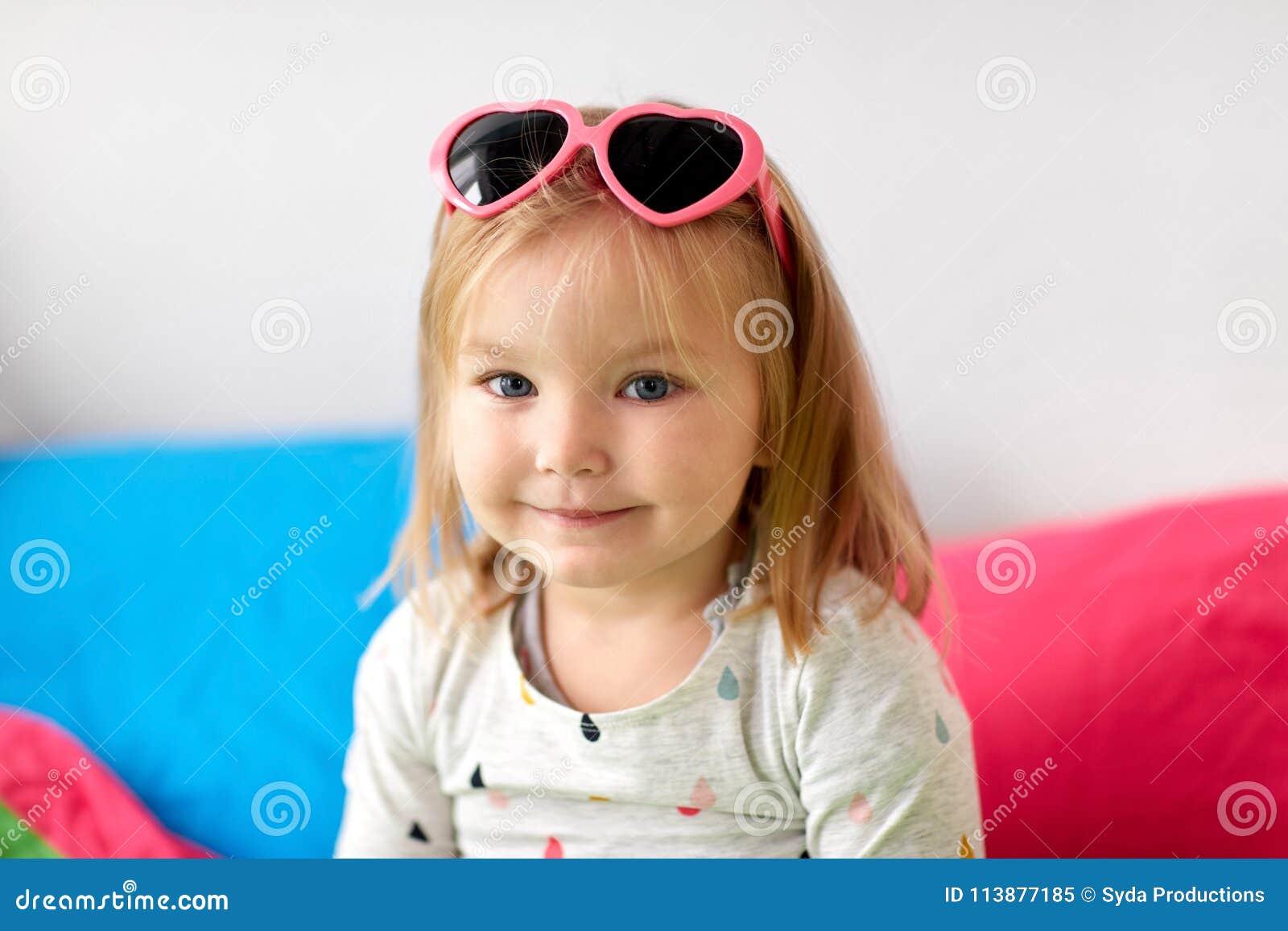 332ebf81d0 Enfance et concept de personnes - portrait de petite fille de sourire  heureuse avec les lunettes de soleil en forme de coeur