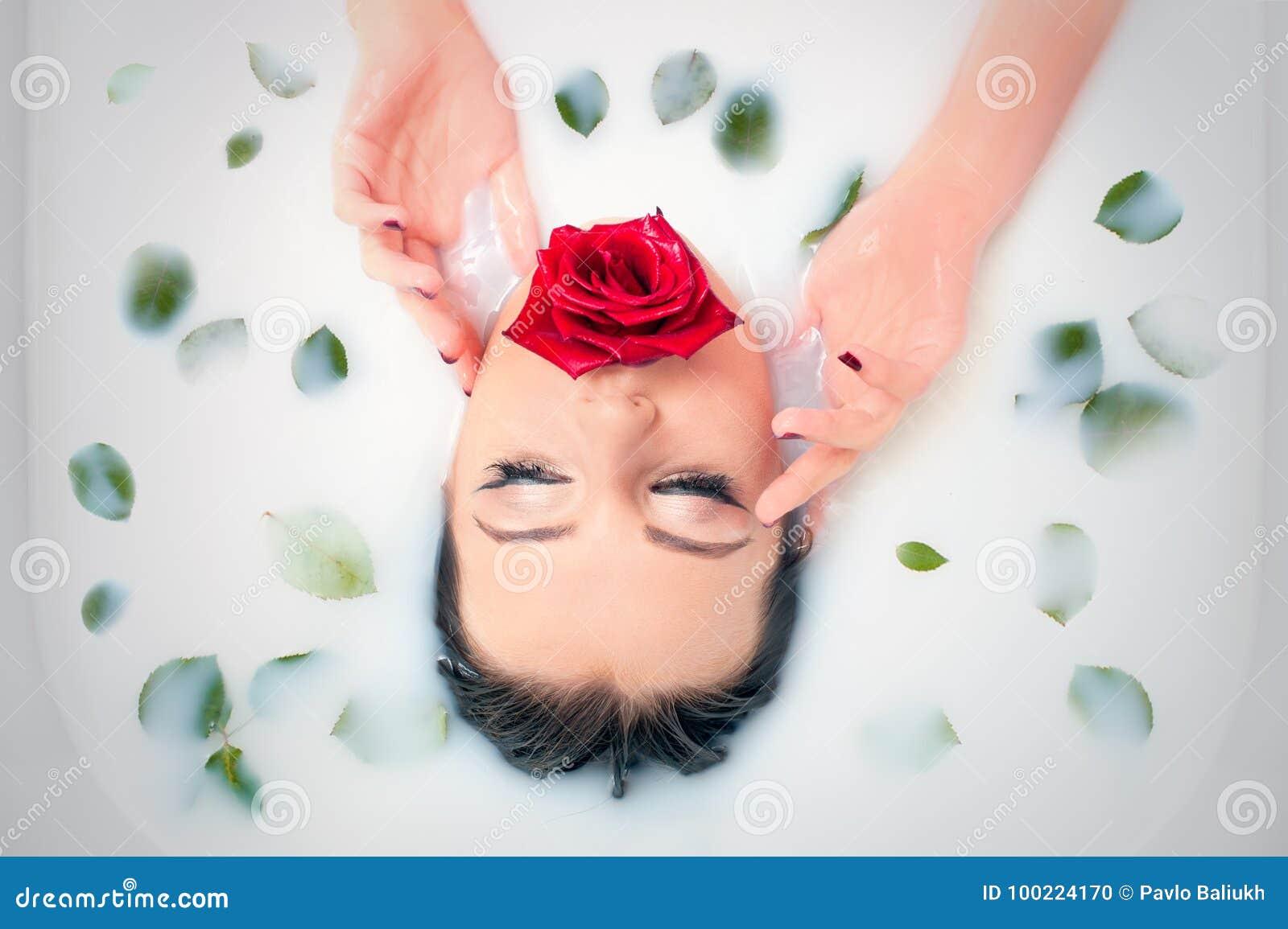Portrait de plan rapproché de charme dans le bain de lait avec et des pétales de rose de feuilles