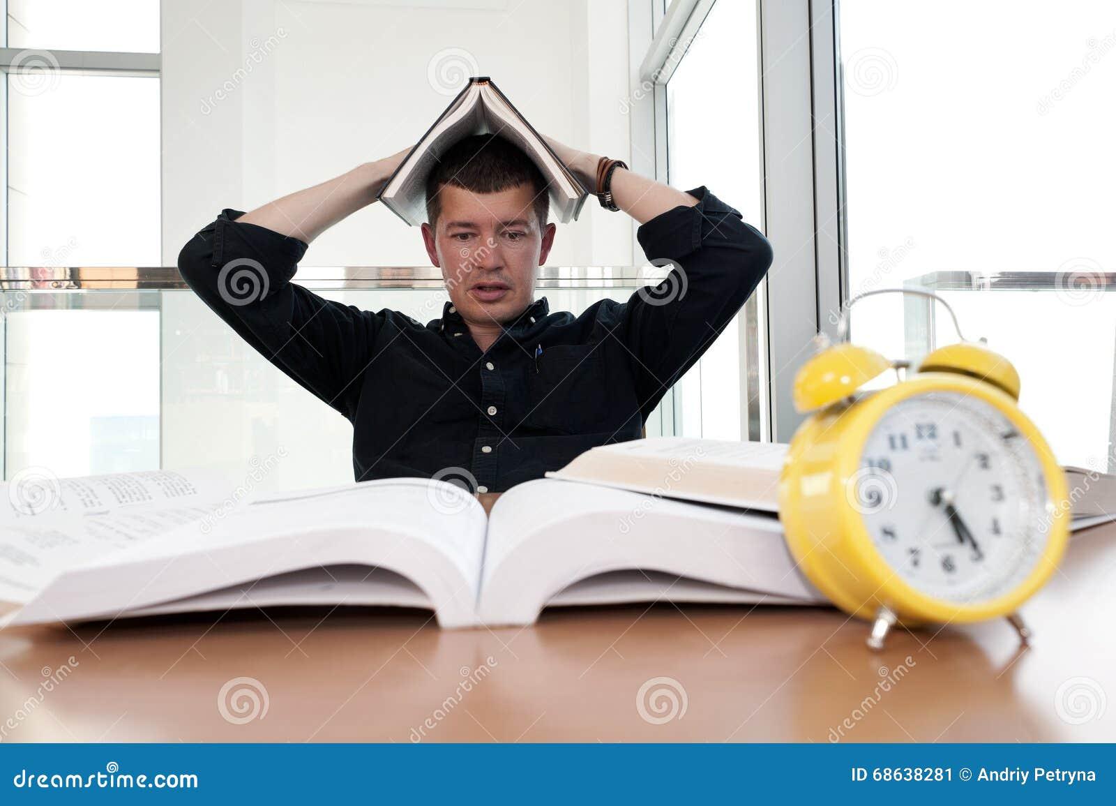 Portrait de plan rapproché de l homme blanc entouré par des tonnes de livres, réveil, soumis à une contrainte de la date-butoir d
