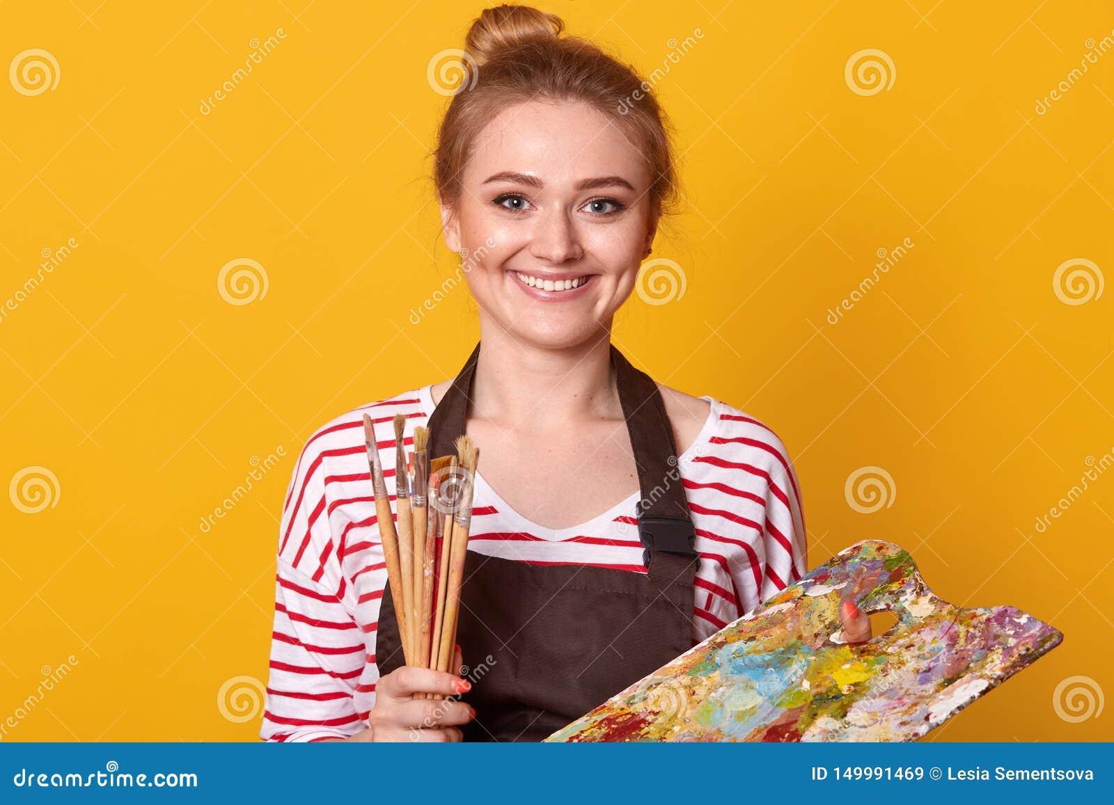Portrait de plan rapproché du peintre mignon adorable positif utilisant le pull molletonné dépouillé, tablier brun, accessoires,