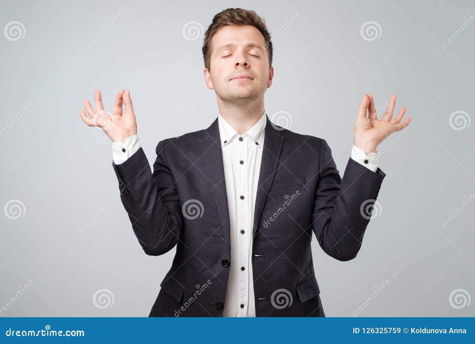Portrait de plan rapproché de jeune mâle beau dans le costume, dans la pose de méditation, détendant, dans le zen, d isolement su