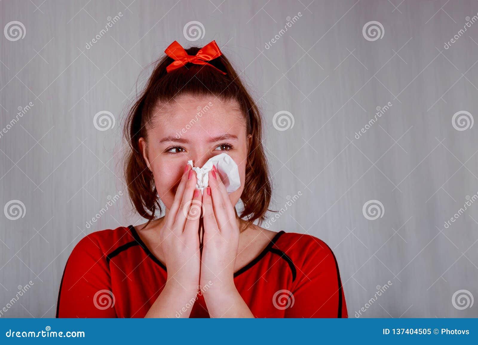 Portrait de plan rapproché de jolie fille éternuant ou employant la serviette pour essuyer la morve de son nez