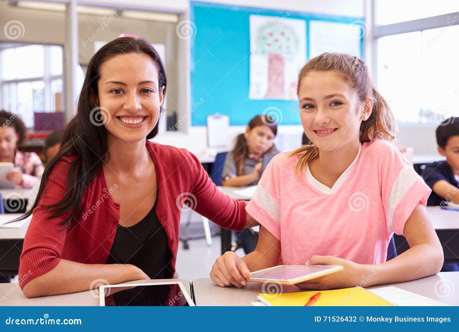 portrait de professeur avec la fille d 39 cole primaire son bureau photo stock image 71526432. Black Bedroom Furniture Sets. Home Design Ideas