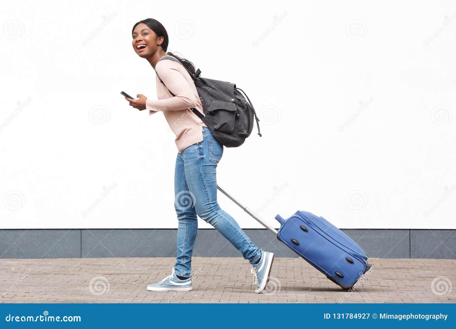 Portrait de profil du jeune voyageur féminin marchant avec le téléphone portable et la valise contre le mur blanc