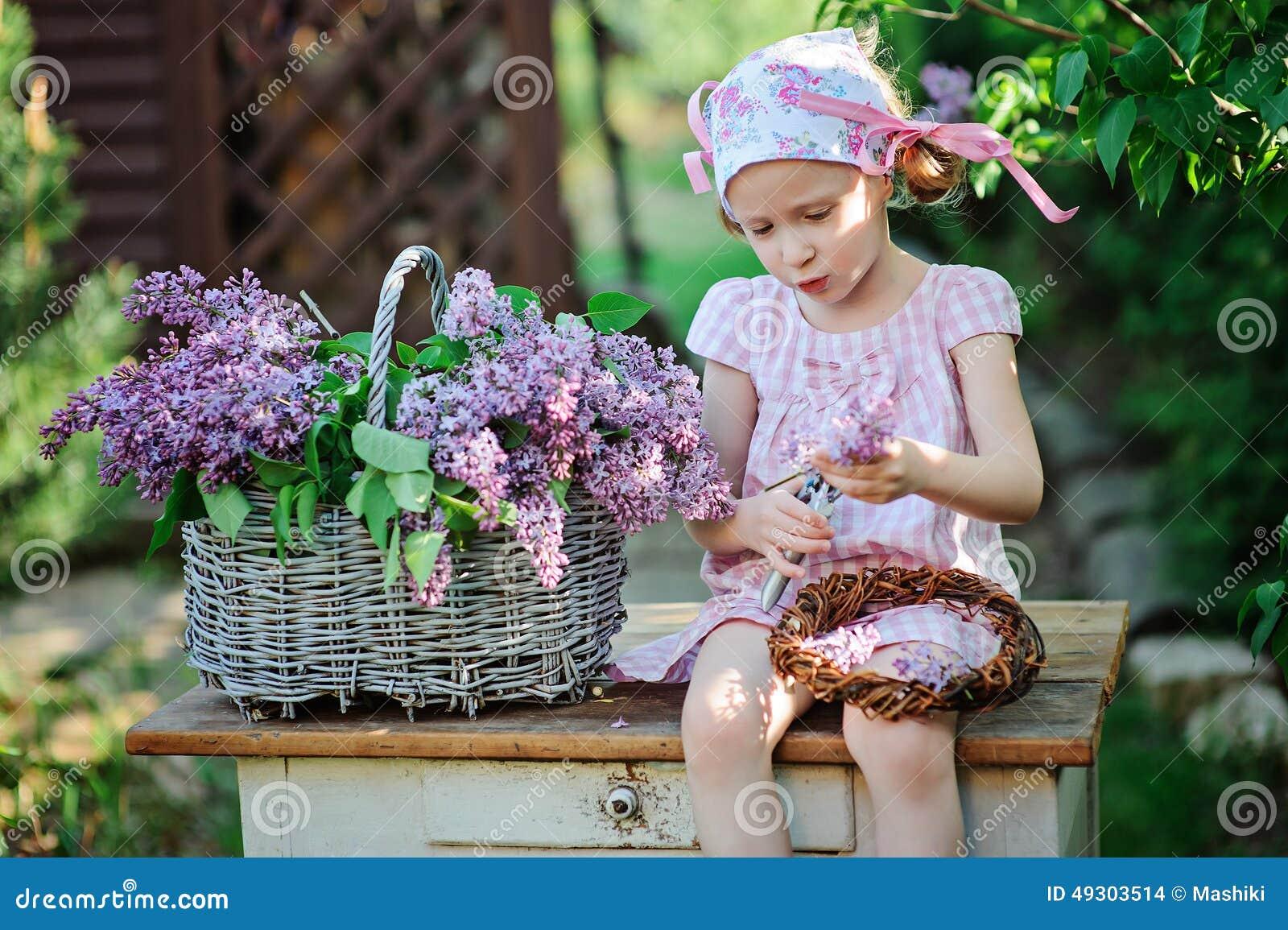 Portrait de ressort de fille adorable d enfant dans la robe rose faisant la guirlande lilas dans le jardin ensoleillé