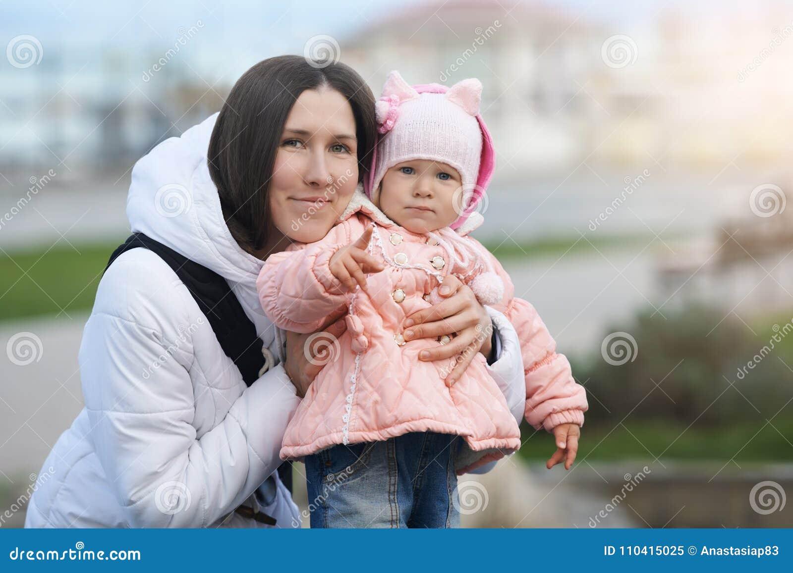 Portrait de rue de la mère de sourire avec sa fille sérieuse Différence d humeur